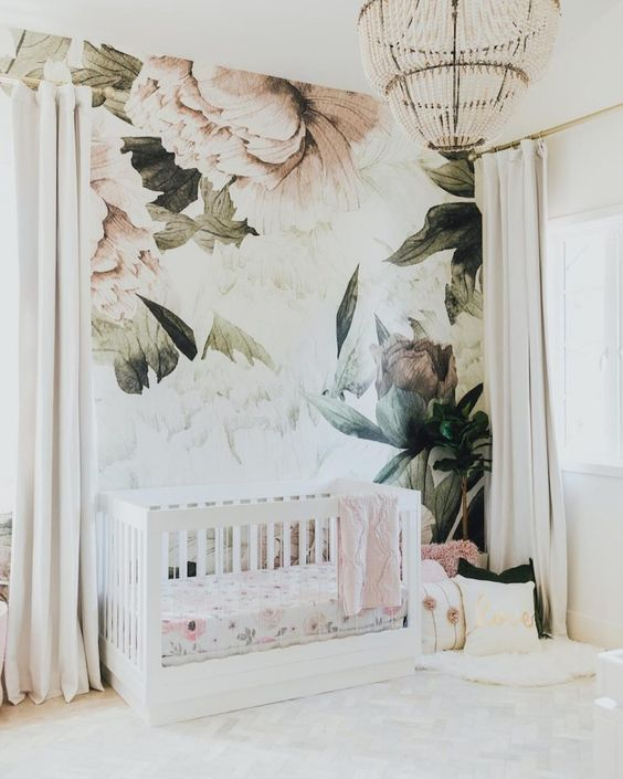 a neutral and airy nursery with a floral wall mural that sets the tone in the space and makes it cooler
