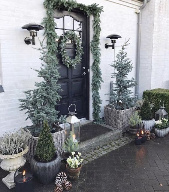 a pale winter front door with an evergreen garland and wreaths, Christmas trees, candle lanterns and pinecones