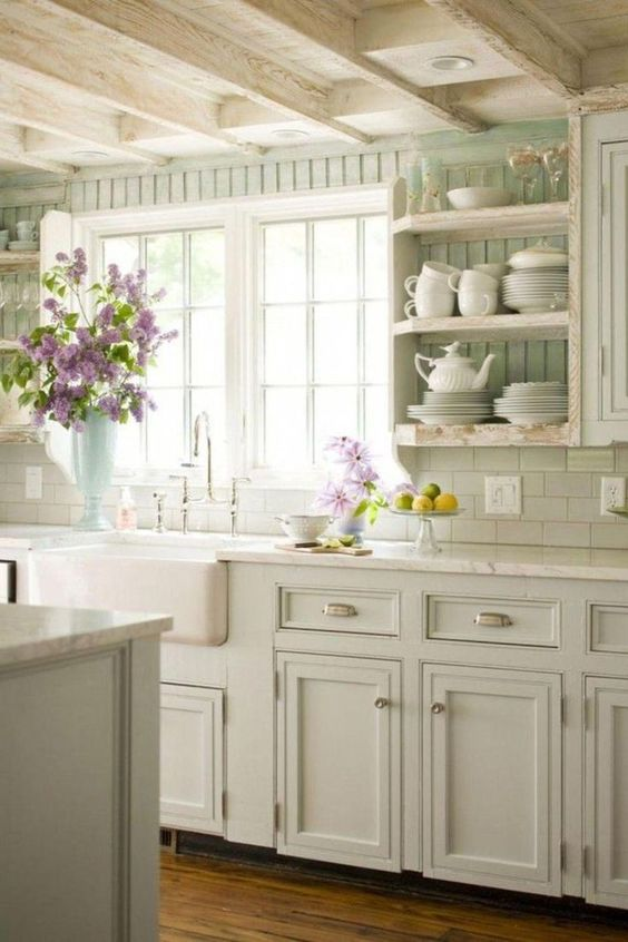 a pastel cottage kitchen with light green shaker cabinets, a beadboard backsplash, open shelves and neutral stone countertops