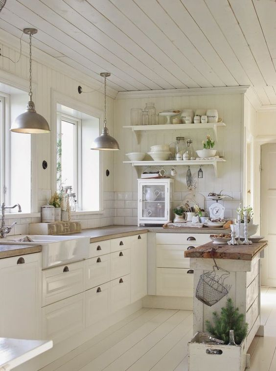 a pretty cottage kitchen totally in white, with a tile cabinet, butcherblock countertops, open shelves and pendant lamps