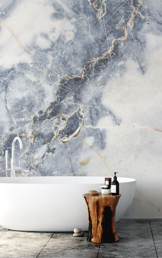 a refined bathroom with a fantastic marble wall, a free-standin bathtub and a tree stump stool or side table