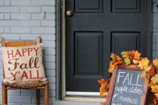 a sign decorated with fall leaves, a crate with blooms and a pumpkin, a fun pillow and a plywood pumpkin sign on the door