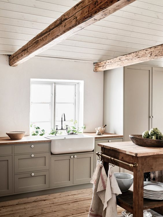 a simple country chic kitchen with a planked ceiling and decorative beams, with grey shaker cabinets and butcherblock countertops, a stained kitchen island