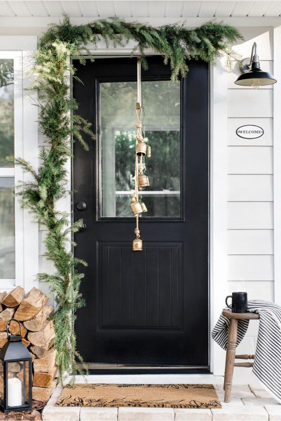 a simple rustic front porch with a fir garland, firewood, a candle lantern, bells and a wooden stool with a blanket
