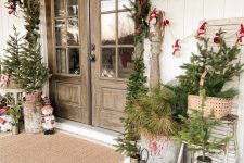 a vintage rustic front porch with mini trees and fir branches in baskets and buckets, candle lanterns, a fir garland, red touches