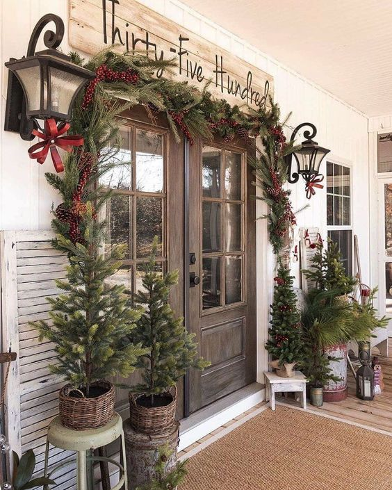 a vintage rustic porch with lots of Christmas trees in baskets, fir branches in a a bucket, lanterns, a fir garland with berries around the door