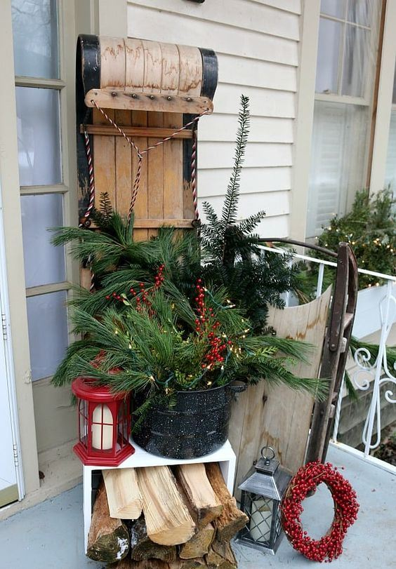 a vintage sleigh, a bucket with fir branches and berries, firewood, a red lantern,a berry wreath for a cozy rustic feel