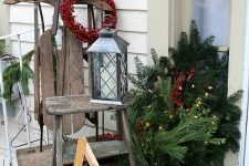 a vintage sleigh, a woodne star and a ladder, a candle lantern, a bucket with fir branches and lights and red ornaments in a box