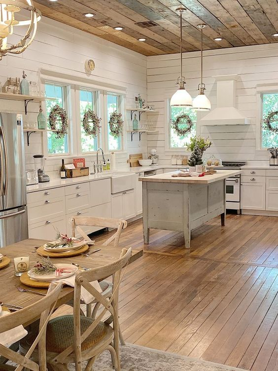 a welcoming cottage kitchen with white planked walls, shaker style cabinets, a shabby chic kitchen island, pendant lamps hanging from a reclaimed wooden ceiling