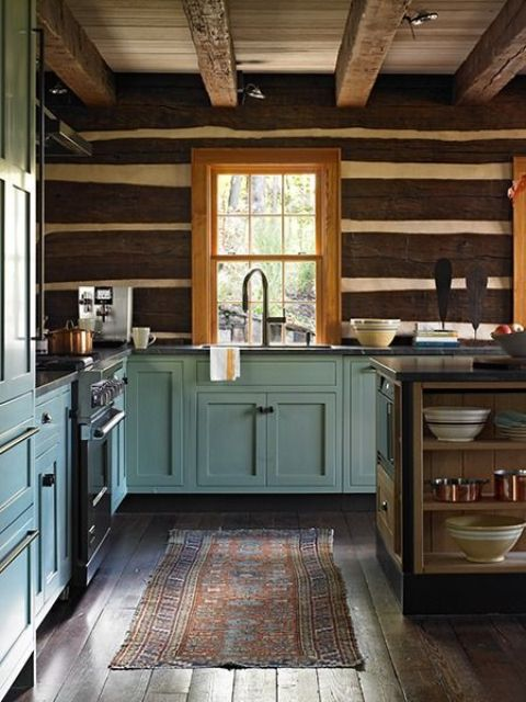 a welcoming cottage kitchen with wooden beams on the ceiling, dark stained planks on the walls, blue shaker style cabinets and a small kitchen island with open storage compartments