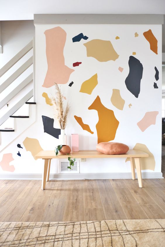 a welcoming entryway with a colorful terrazzo wall mural that brings a fun touch and a bit of color to the space