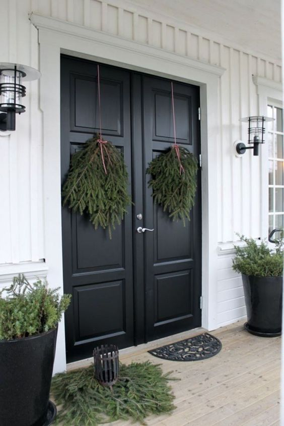 all-natural Christmas front door decor with evergreen posies, some evergreens on the floor and in pots