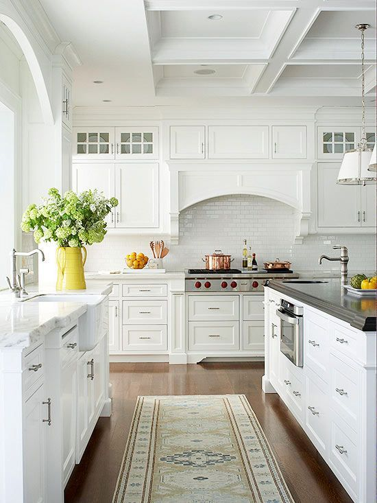 an enchanting cottage kitchen with white shaker cabinets, a coffered ceiling, a large kitchen island with a contrasting countertop and greenery