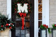 an evergreen wreath with red ornaments, a red bow, a monogram and candles with red ornaments inside