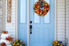 bold fall blooms in pots, white pumpkins stacked with fall leaves, a wreath fo fall leaves and with a bow