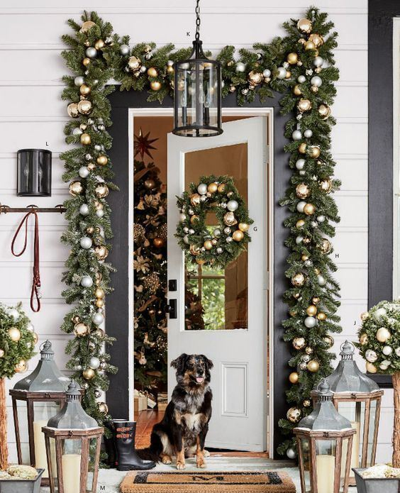bright and festive Christmas front door decor with evergreen garlands and metallic ornaments, topiaries and candle lanterns