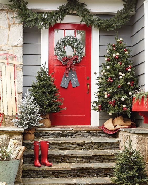 cozy Christmas front door decor with an evergreen garland, mini trees and a large one with red and white ornaments plus a snowy wreath