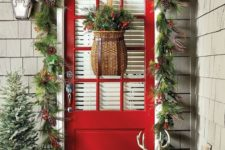 cozy rustic Christmas front door styling with an evergreen garland with berries and pinecones, a snowy mini tree and red boots