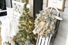 elegant white farmhouse Christmas decor with a white sleigh with a flocked wreath and lights, a white lantern, a mini tree with lights, a bucket with branches and a white bench with a blanket