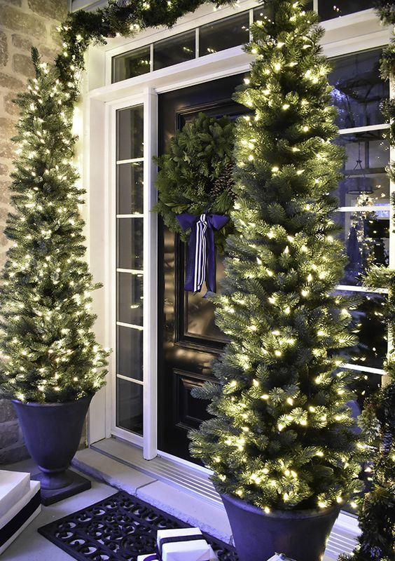 evergreen garlands with lights, Christmas trees with lights in pots and gift boxes for a cozy holiday feel