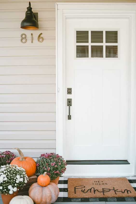 fall blooms in pots and some pumpkins plus a mat will make your porch Thanksgiving-ready