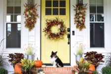 fall posies and a wreath with foliage, berries and feathers, fall blooms and plants in pots and pumpkins on the steps
