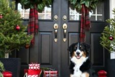 farmhouse Christmas front door with magnolia leaves wreaths and scarves, evergreen garlands, a Christmas tree with red ornaments and lots of gift boxes