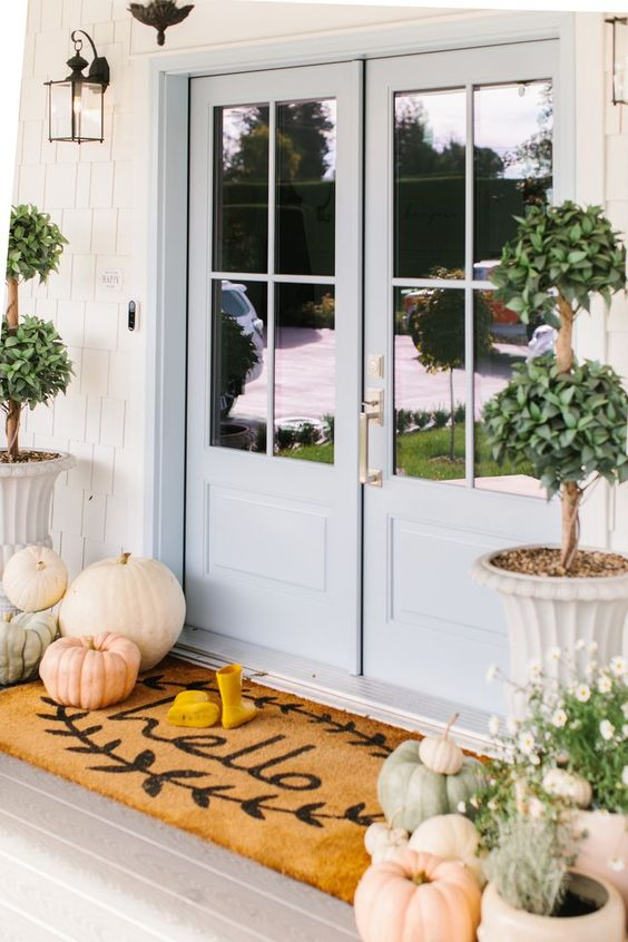 heirloom pumpkins, greenery in pots and a mat for natural Thanksgiving decor