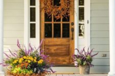 heirloom pumpkins on the steps, bold fall bloom arrangements in buckets, a fall wreath of berries on the door