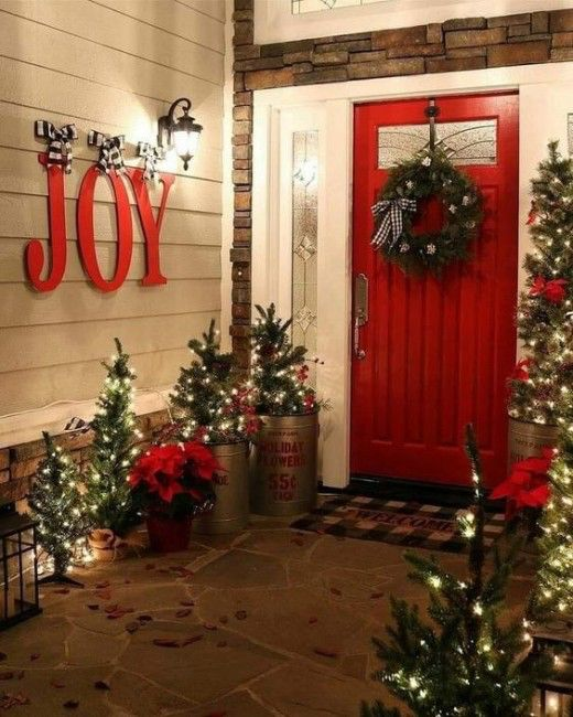 lots of mini Christmas trees with lights, JOY letters, a wreath and red touches for a lovely rustic front porch
