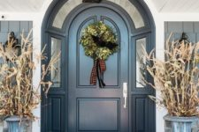 lots of natural pumpkins on the floor, corn husks in vintage urns and a greenery wreath with plaid ribbons in the door