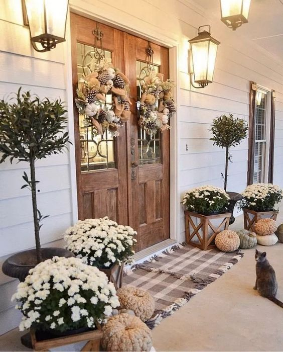 neutral pumpkins, white blooms in pots, wreaths of burlap, pinecones and white pumpkins for Thanksgiving