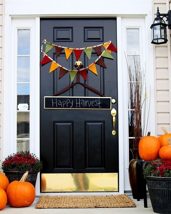 orange pumpkins, bold fall blooms in pots, a colorful bunting and a chalkboard sign for simple Thanksgiving decor