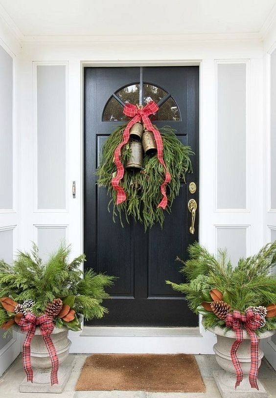 rustic Christmas front door styling with large bells, evergreens, snowy pinecones and magnolia leaves plus plaid ribbons