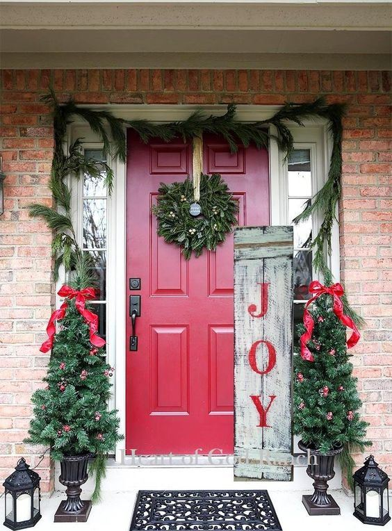 rustic Christmas front porch decor with an evergreen garland, mini trees with red ornaments and bows, a sign and candle lanterns