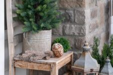 rustic vintage porch decor with oversized pinecones, greenery balls and a mini tree in a bucket plus wooden candle lanterns