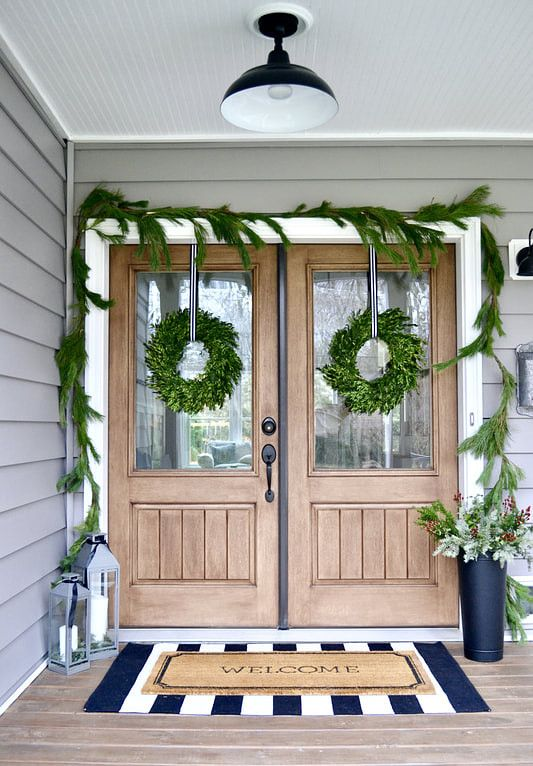 simple natural Christmas front door styling with an evergreen garland and wreaths, candle lanterns and a pale greenery arrangement