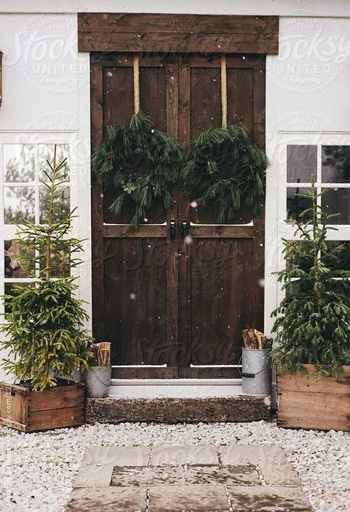 simple rustic front porch decor with Christmas trees in crates, buckets with firewood, fir wreaths on ribbons looks al-natural