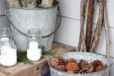 some branches, firewood in a bucket, a bucket with pinecones, candles in glass jars and fir branches for a cozy feel in the porch