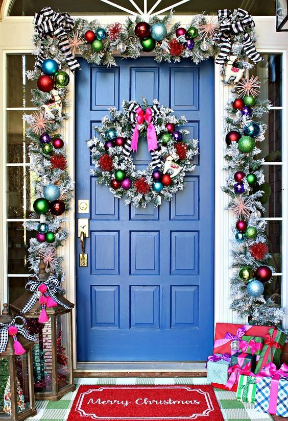 super bright Christmas front door decor with a silver garland with colorful ornaments, striped bows and  a matching wreath plus colorfil gift boxes
