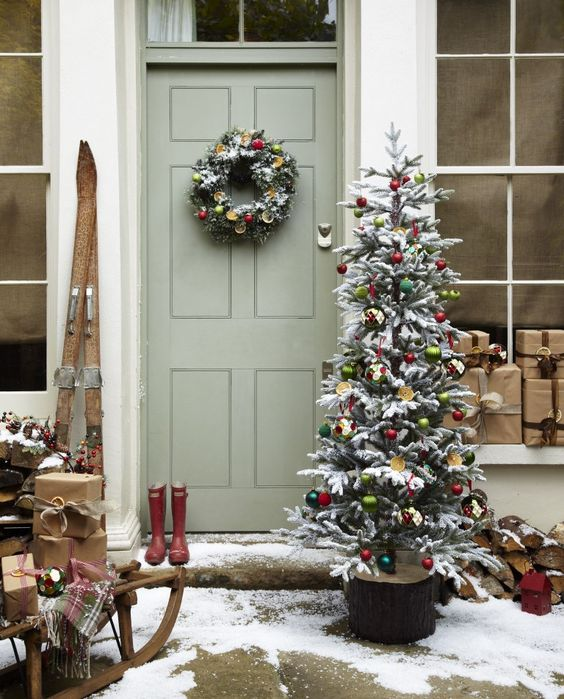 vintage-inspired Christmas front door decor with a cute wreaht with citrus slices and ornaments and a Christmas tree decorated with them, a sleigh with gift boxes and skis