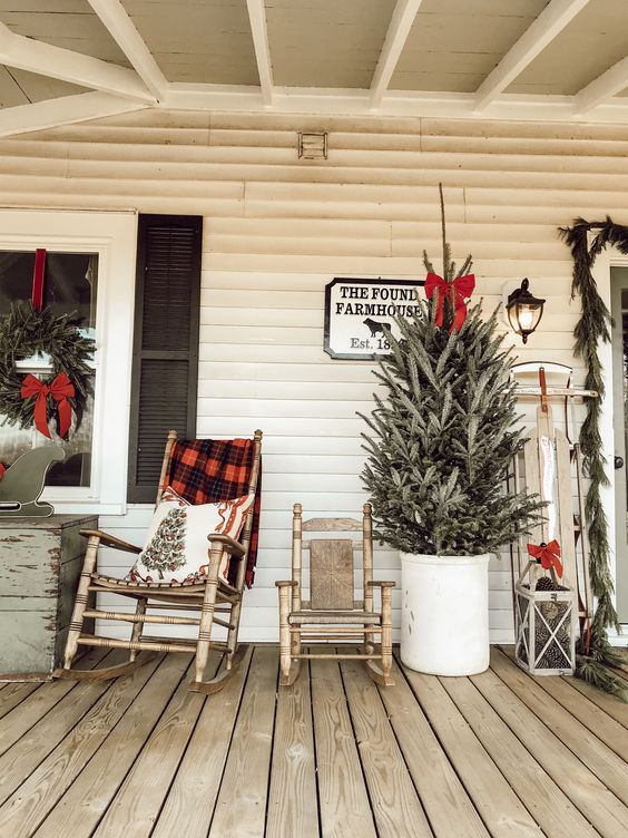 wooden rockers with a plaid blanket and a printed pillow, a Christmas tree in a bucket with a red bow, a vintage sleigh with a bow and a wreath