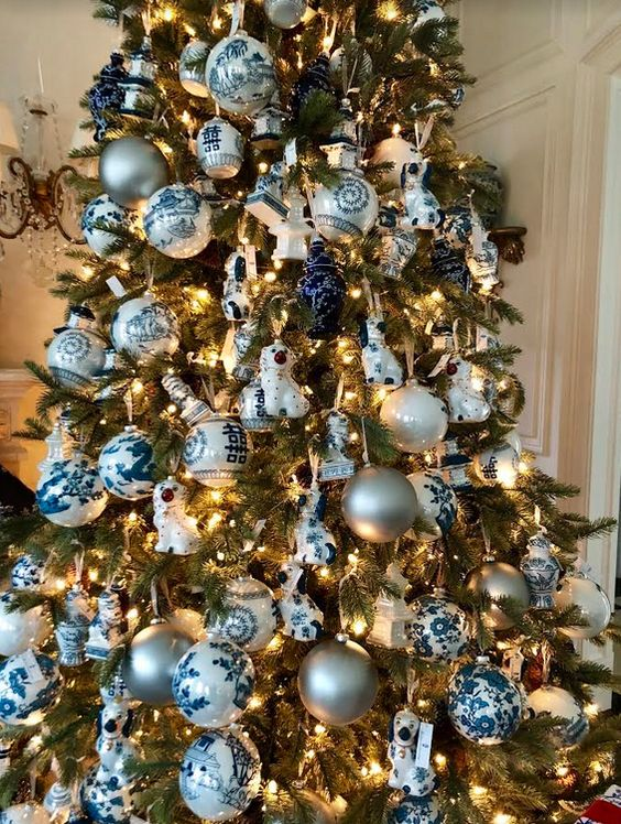 a Christmas tree decorated with lights, blue and white plus silver ornaments, ribbons and porcelain pieces is lovely
