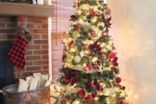 a Christmas tree with lights, gold ribbons, red, neutral and gold ornaments, poinsettia and stars