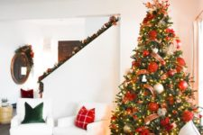 a Christmas tree with lights, red and gold ornaments, ribbons and a shiny snowflake topper