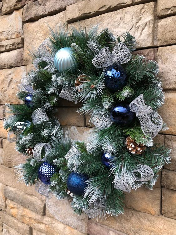 a Christmas wreath with bold blue and light blue ornaments, pinecones and silver ribbons is a lovely and chic idea
