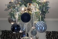 a beautiful Christmas chandelier of navy, light blue and silver ornaments, frozen branches, twigs and candles is wow