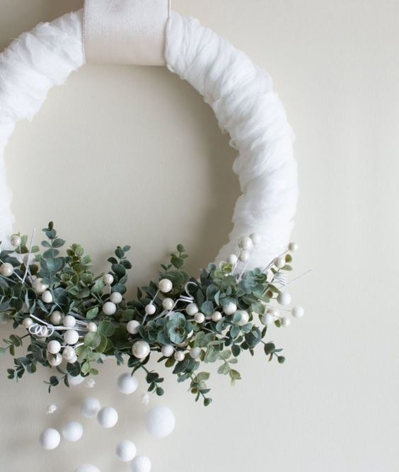 a beautiful winter wreath in white, with lush greenery, snowballs and beads is a lovely option for Christmas front door decor