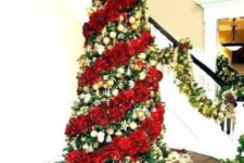 a bold Christmas tree with gold ornaments and a fluffy red garland plus a large red bow on top