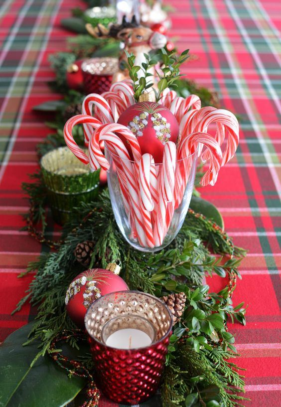 a bold and pretty festive centerpiece of greenery, fir branches, red ornaments, candles and candy canes is very chic
